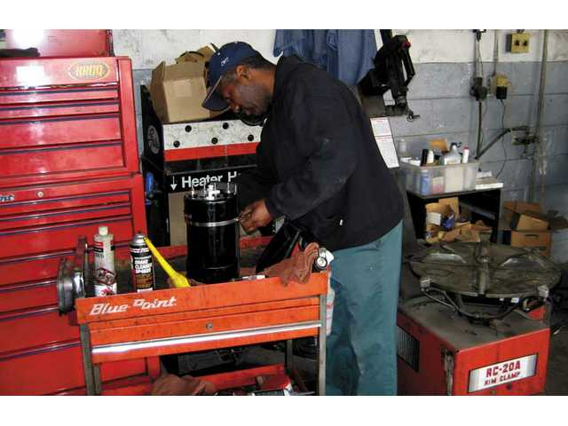 Auto Service Plus employee Ray Pruitt works on a hybrid converter. The device fits on the back of a car's front bumper. Auto Service Plus owner Larry Totter hopes the device will help break drivers' dependence on gasoline.