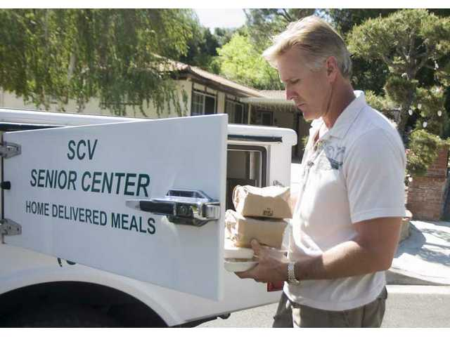 Mike Crone, makes a delivery on April 21 in Newhall. Crone has been volunteering in the SCV Senior Home Delivered Meal program since August 2008.