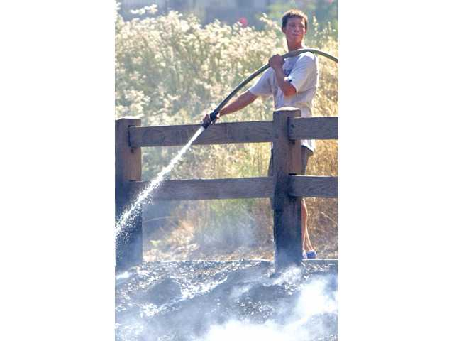 Newhall resident Josh Hahn, 17, helps put out a fire that burned 5 acres at the Valencia Summit Park recently.