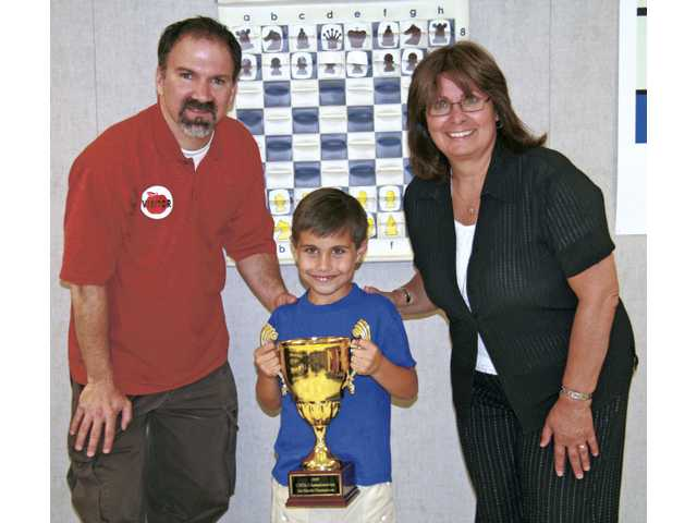 First-grade champion Jackson Dow celebrates with Coach Jay Stallings and Principal Alexis Yannic after receiving top honors at the California Youth Chess League Championships.