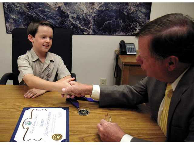 Hunter Throckmorton, shakes hands with Mayor Bob Kellar after being awarded the title of The Most Philosophical Fourth Grader in America. The Valencia Meadows student earned the prize by writing an essay on global warming.
