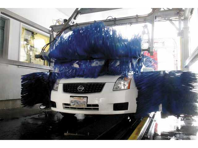 A vehicle runs through the car wash at the Valencia Auto Spa on Tuesday. The Newhall County Water District is pondering cracking down on residents washing their vehicles at home, which may mean the only way for some to clean their car will be at a car wash.