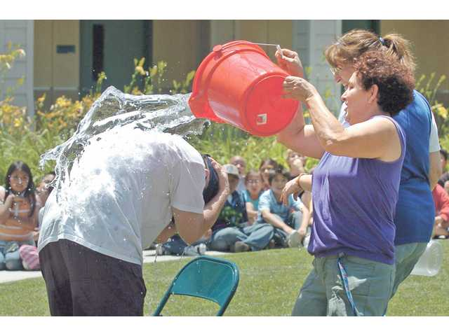 Watching their students struggle to hit their target was too much to bear for several faculty members, who filled water buckets and joyfully soaked their boss to the delight of students and their peers.
