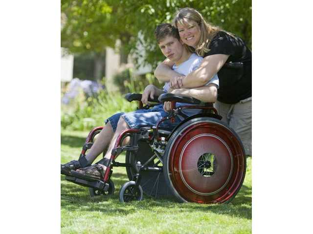 "Twenty-two-year-old Robbie Argote-Carrillo and his mom Stacee Carrillo embrace outside their Canyon Country home with his new custom made wheelchair designed by Steve Flanagan of the television show ""Paint Misbehavin'."""