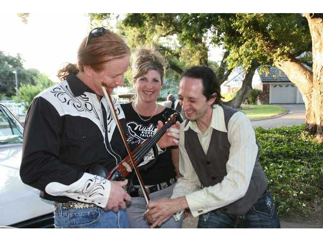 Guitarist/singer Michael Lyn, Jamie Nudie and violinist Philip Vaiman horse around with Phil's instrument at Evening Under the Oaks.