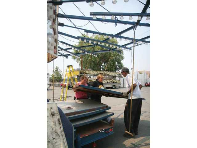 Kathy Rolin, Renee Wody and Terry White help build the carousel, for this weekend's Valley Fair.