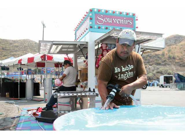 Alberto Sanchez, from Fresno, helps wash parts of the Dandy Souvenirs stand, Wednesday afternoon, preparing for this weekend's Valley Fair at the Saugus Speedway. The annual fair opens today.