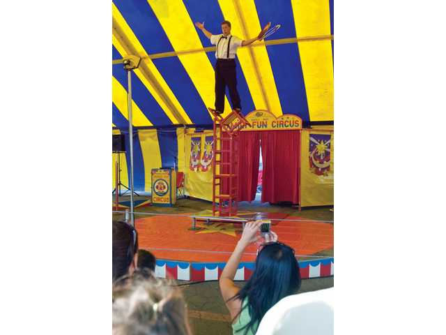 Bobby the clown performs his chair balancing act at the Valley Fair on Thursday at the Saugus Speedway.Right: Michale Bowen with her son Donny from Frazier Park enjoy some of the games at the fair.