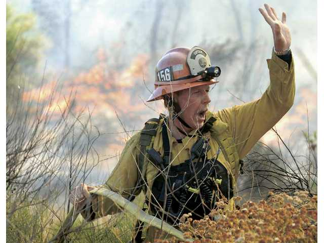 Capt. Michael Siefert of L.A. County Fire Station 156 calls for water at a five-acre brushfire near Bridgeport Lane and McBean Parkway in Valencia on Friday.