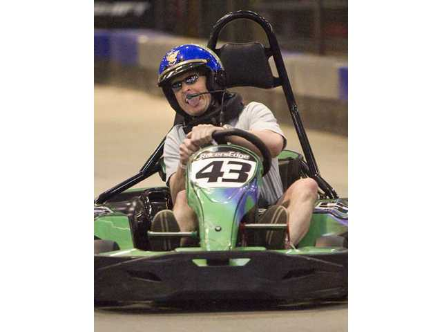 "California Highway Patrol's Sergeant Matthew Hill speeds through the Racer's Edge Indoor Karting course, in Canyon Country, during Thursday night's ""First Responders Fast and Furious"" charity event. Personnel from the Los Angeles Sheriff's Department, Santa Clarita Valley Station, California Highway Patrol, American Medical Response and L.A. County Fire Department raced one another and other locals who donated money to benefit the 999 for Kids program."