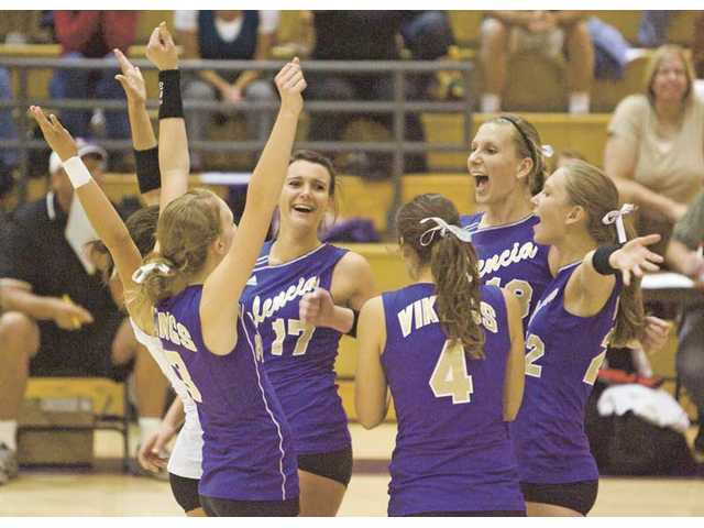Members of the girls volleyball team celebrate after a point last fall. Valencia won its seventh consecutive league championship.