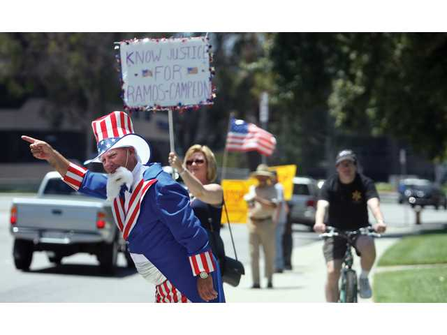 Saugus resident Geoff Wilson, dressed as Uncle Sam, waves to passing cars, urging them to wave or honk at the Honor America/ Secure Our Border rally. The event took place at the SCV Civic Center on Saturday.