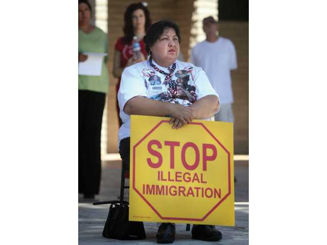 Lupe Moreno, from Santa Ana, listens as guest speakers talk at the Honor America/Secure our Borders rally.