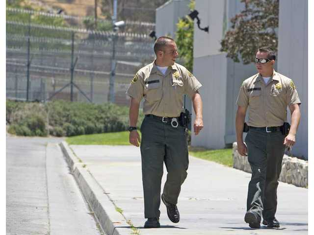 Deputies Gruppie, left, and Round walk through Pitchess Detention Center's North Facility on Monday afternoon. The medium security facility, which holds 1,600 inmates, may be closing in the near future if the Los Angeles County Board of Supervisors will not take back a $25 million budget cut.