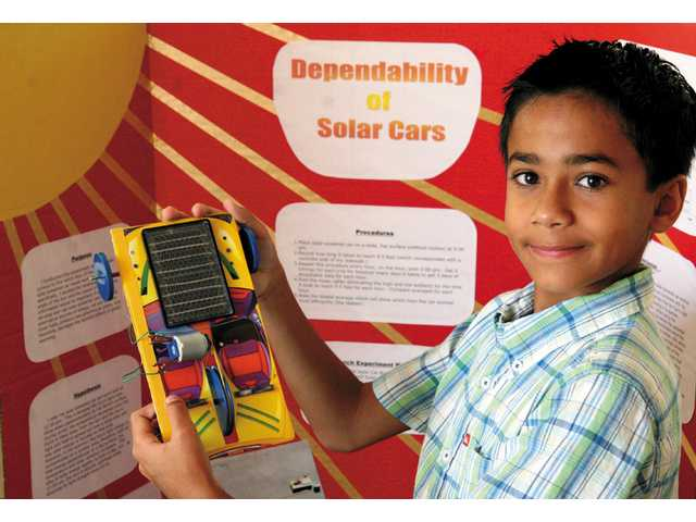 Recently graduated Helmers Elementary School student Aleem Zaki shows off his solar car project which made it to the State Science Fair held in Los Angeles.