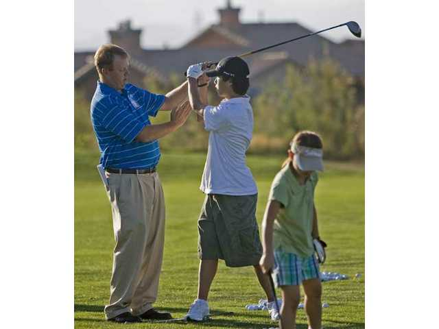 Ross Bradder, left, gives pointers to Stevenson Ranch resident Clay Kim, 13, at the driving range at TPC Valencia Friday evening. Bradder, a local golf businessman, has established a youth golf training academy for junior players in the area.