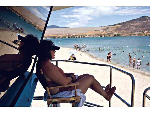 Renee Danganan, 28, watches over visitors at lower Castaic Lake as they escape the heat.