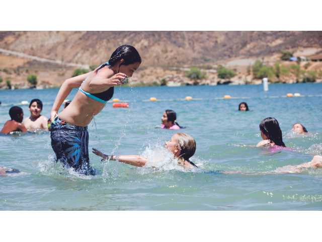 Children play tag in lower Castaic Lake on Tuesday.