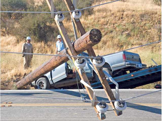 California Edison employees Gordon McNeill, left, and Mike Hughes assess a knocked down power line on San Francisquito Road just north of Copper Hill Drive. An unidentified male lost control of his truck and crashed into it shortly after 4:30 p.m. on Tuesday.