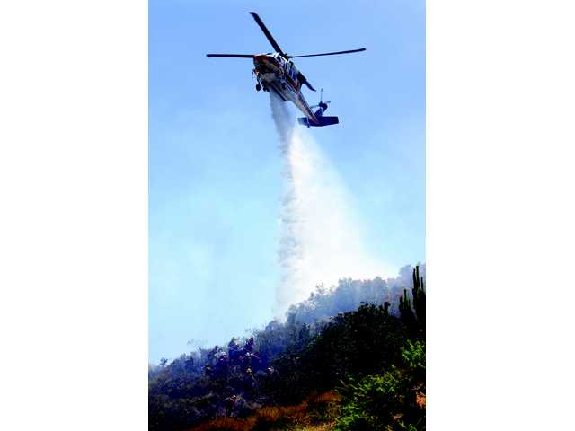 The Los Angeles County's Firehawk drops a payload of water along a hot spot in Sand Canyon Tuesday.