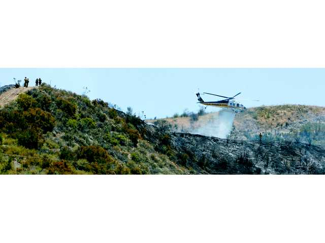 Handcrews work to cut a fireline along a hillside as the Los Angeles County's Firehawk drops a payload of water along a hot spot in Sand Canyon on Tuesday. Firefighters contained the fire, which threatened  several homes, to 3 acres.
