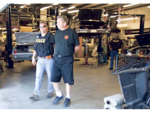 A Taskforce For Regional Auto-theft Prevention detective escorts Nellson Vels out of his auto shop, Billet Works Performance, located in the Canyon Country  industrial center on Wednesday.