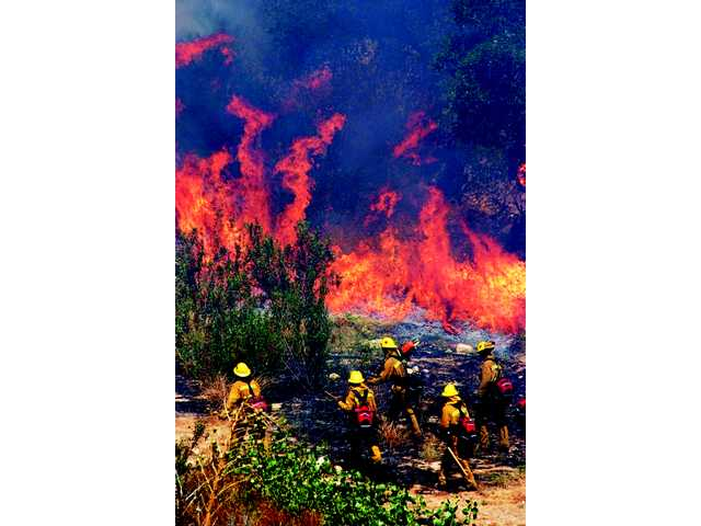 Los Angeles County firefighters and air support work to control brush fires below homes at Deputy Jake Drive and Kirsch Court in Newhall. No homes were damaged, and no were injuries reported.