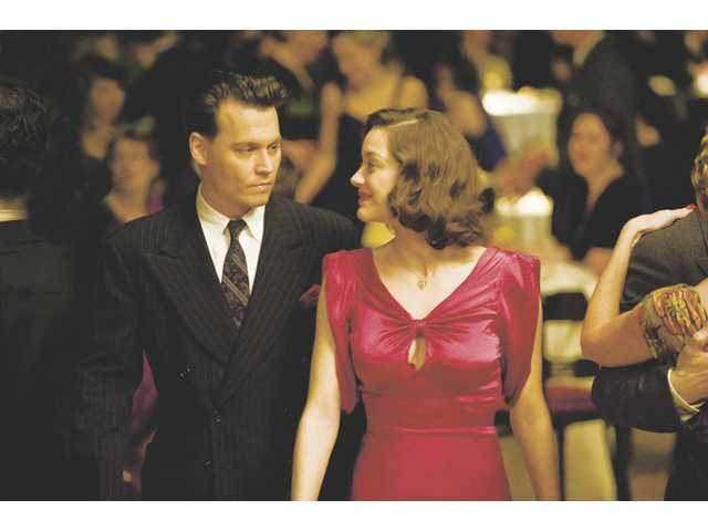 "Johnny Depp as John Dillinger and Marion Cotillard as Billie Frechette in ""Public Enemies."" The film has earned praise from the critics, including Roger Ebert."