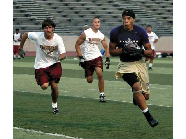 Valencia High School's receiver Zack Tartabull runs the ball toward the end zone, as he makes his way past two Alemany High players, during Day Two of the Hart Passing Tournament on Wednesday at College of the Canyons.