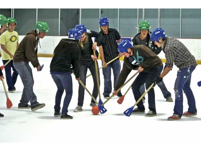 A group of high school students compete against each other in a game of broomball at Grace Baptist Church's youth group night.