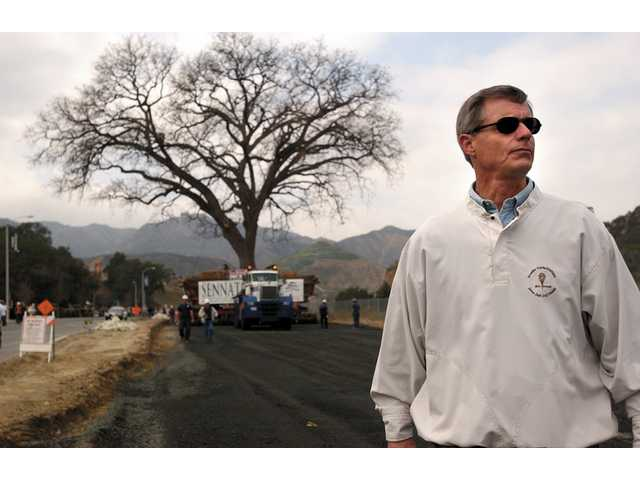 Bill Ratazzi, regional president of John Lang Homes, watches the path 'Old Glory' takes down Pico Canyon Road to its new home 1/4 of a mile away from the tree's original resting spot.