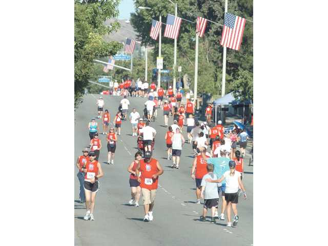 Runners and walkers alike work to raise money for the Hart district during the July Fourth 5K run.
