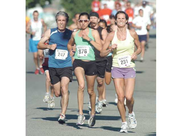 Hundreds of runners participated in the Santa Clarita Runners Independence Day 5K, shown heading east on Lyons Avenue on the parade route before the July Fourth parade Saturday.