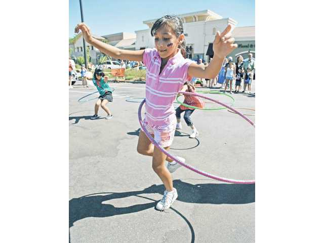 Melissa Espinoza, 9, competes for a $20 Bristol Farms gift certificate in a hula hoop contest held at the Fourth of July Picnic & Carnival sponsored by Bristol Farms and Bridgeport Marketplace and held in their parking lot on Saturday.