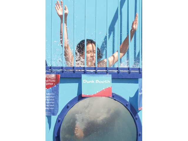 Stacy Indermill, 14, drops in to a dunking booth fundraiser for Hart High girls volleyball at the Bristol Farms and Bridgeport Marketplace Picnic and Carnival held in the parking lot on Saturday..