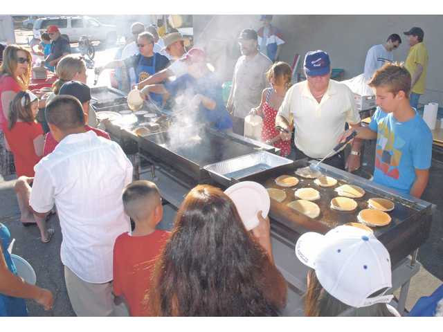 Jorgen Christensen and Charles Norris, 16, right, work the griddle as they prepare  some of the hundres of pancakes served at the 44th annual Rotary Pancake Breakfast before the Fourth of July parade Saturday morning.