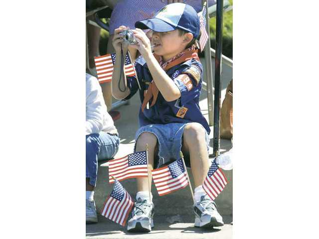 Cub scout Ricky Elan, 7, bristling with flags, takes a picture as a float passes by at the 2009 SCV Fourth of July Parade on Saturday.