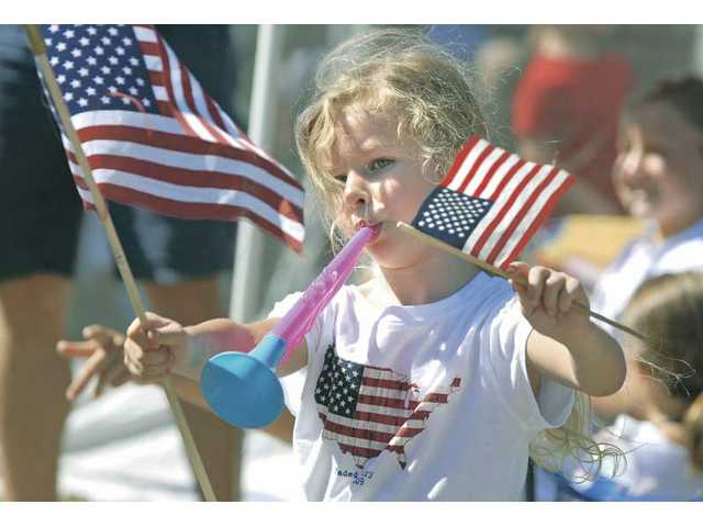 Olivia Grimes, 5, blows her horn and waves her flags on McBean Parkway as she watches the parade pass by.