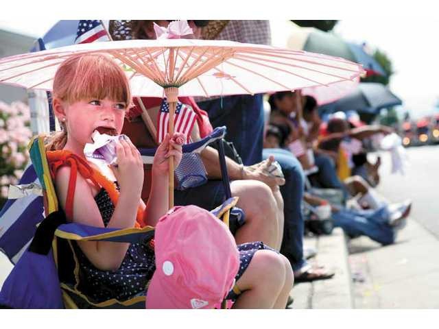 Seven-year-old Ally O'Neill, of Castaic, keeps cool under an umbrella while eating ice cream as the Fourth of July parade kicked off Friday morning in downtown Newhall.