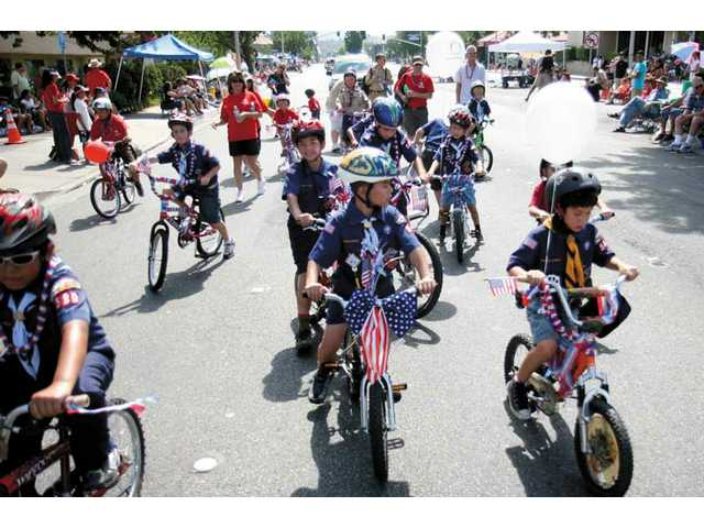 Cub Scout pack 580 members, from Castaic, ride their bikes as they take part in this year's parade in Downtown Newhall on Friday morning.