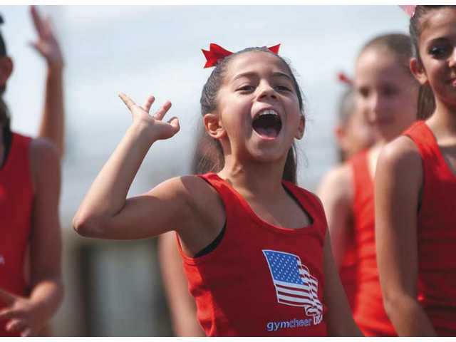 The Gym Cheer USA team pumps up the crowd at the Santa Clarita Valley Fourth of July Parade in downtown Newhall on Saturday.