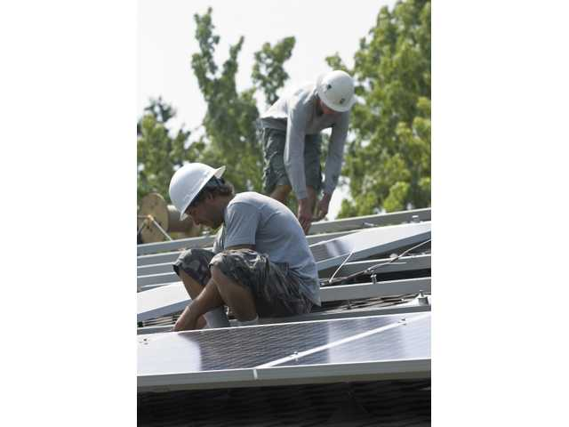 Workers install the solar panels on the roof of B.J. Atkins' home.