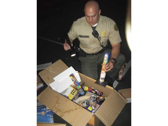 Sheriff's Deputy Brandon Aguilera examines a box of shells and canisters of illegal fireworks and empty beer cans at Valencia Valley Elementary School's playground on Saturday night. Aguilera found multiple groups gathered at the playground watching the illegal fireworks display.