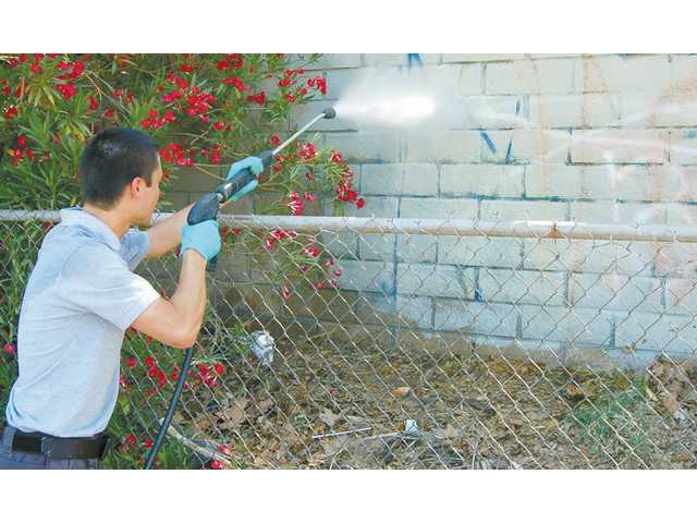 Ryan Faretta, who works for the city's graffiti removal team, uses a pressure washer to remove tags from a wall on Whites Canyon Road in Canyon Country last May. Less than 15 minutes was needed to remove the grafitti.