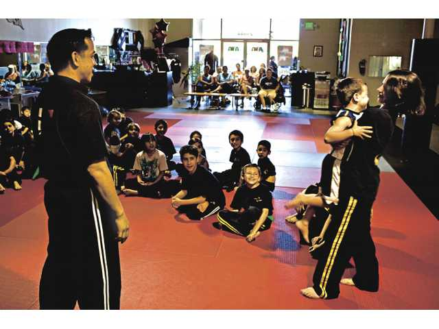 Gavin Espinoza teaches breakaway techniques to Dylan Horowitz, 5, while his sister Ashley, 12, poses as a stranger who is trying to abduct him. ATA Martial Arts Studio hosts a weekly Kidz 'n Power seminar, endorsed by Amber Alert, for kids and parents to learn more about avoiding child abduction.