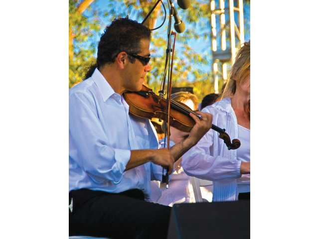 Armen Anassian, first volinist/concertmaster for the Santa Clarita Symphony, looks cool and plays hot at the orchestra's Concert in the Park performance Saturday evening.