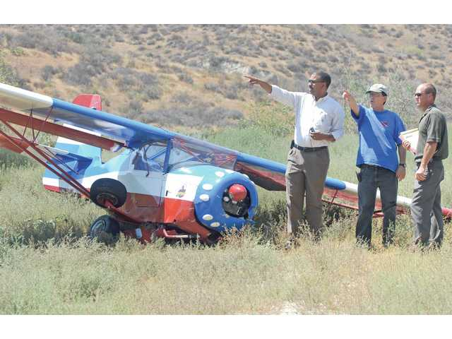 The pilot of a KitFox Speedster, Karl Florine, center, points out the glide path he used to crash land his plane behind Six Flags Magic Mountain on Tuesday. Federal Aviation Administration investigators, Cotry Shearrill, left, and Jerry Badillo gathered information at the scene.
