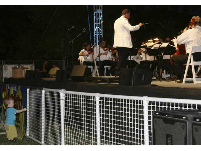 William Biondo of Canyon Country at 20 months is already practicing to take over someday as conductor of his own orchestra, inspired no doubt by Santa Clarita Symphony Maestro Robert E. Lawson (in white jacket) at Saturday's Concert in the Park.