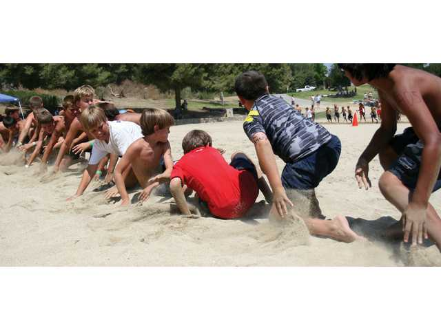 Junior Lifeguards participate in a beach flag event at the annual Castaic Lake Junior Lifeguard Competition on Tuesday at Castaic Lake. Youngsters from several Los Angeles recreation areas took part in the yearly affair.