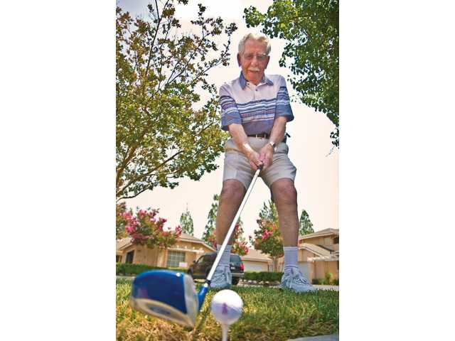 Albert Gandy shows the golf stance that allowed him to hit four holes-in-one in five weeks, Wednesday at his front yard in Saugus.